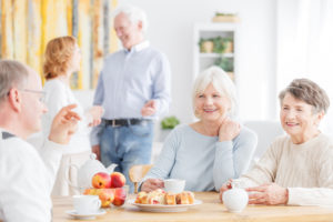 Older people smiling around table